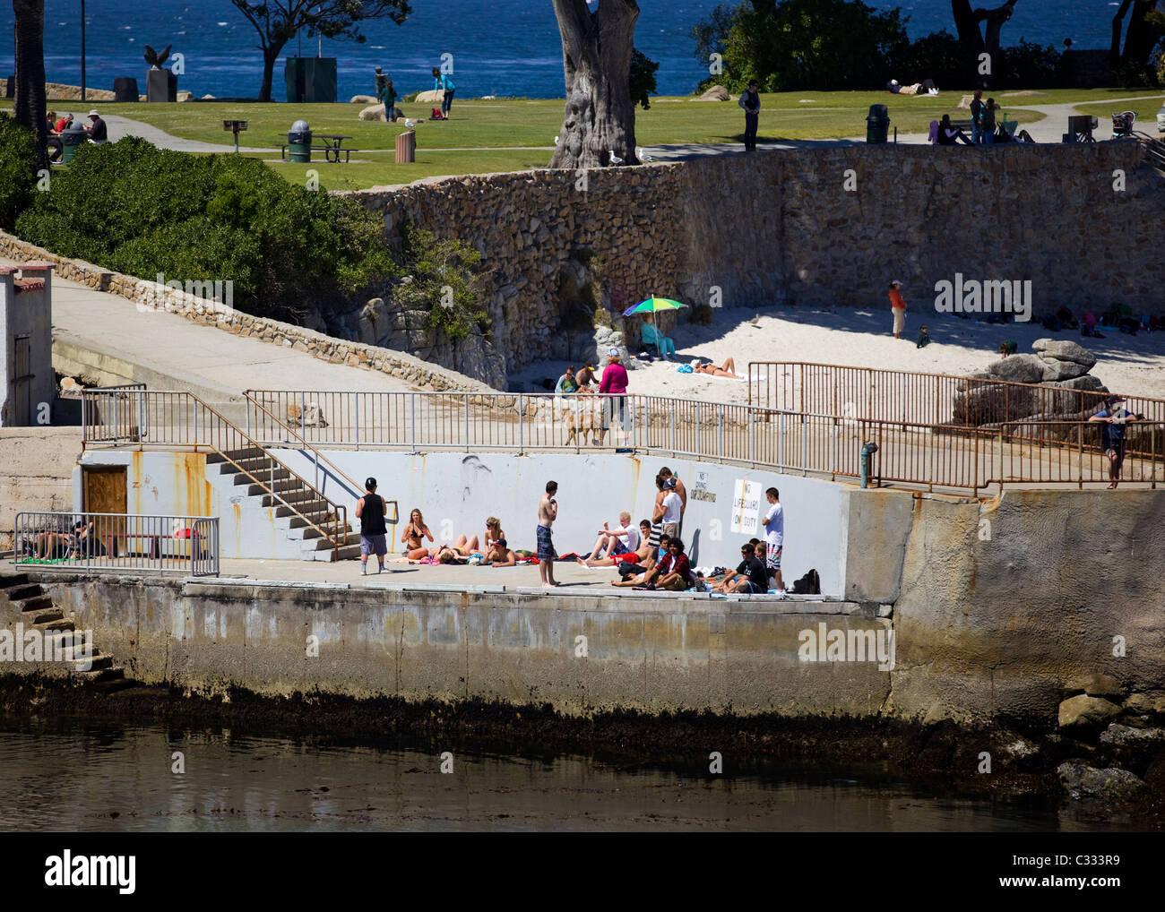 Sunbathers on old concrete boat dock - Monterey, California, USA - Stock Image