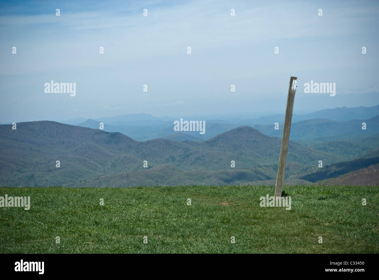 A post with a white blaze is indicating the route of the Appalachian Trail on Max Patch, a Mountain in North Carolina - Stock Image