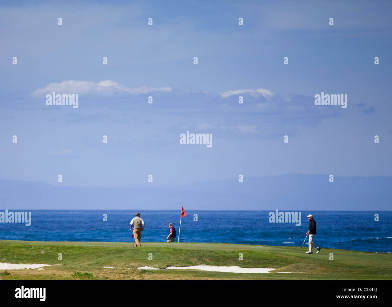 Golfers on putting green on the famous oceanfront Pebble Beach golf course - Stock Image