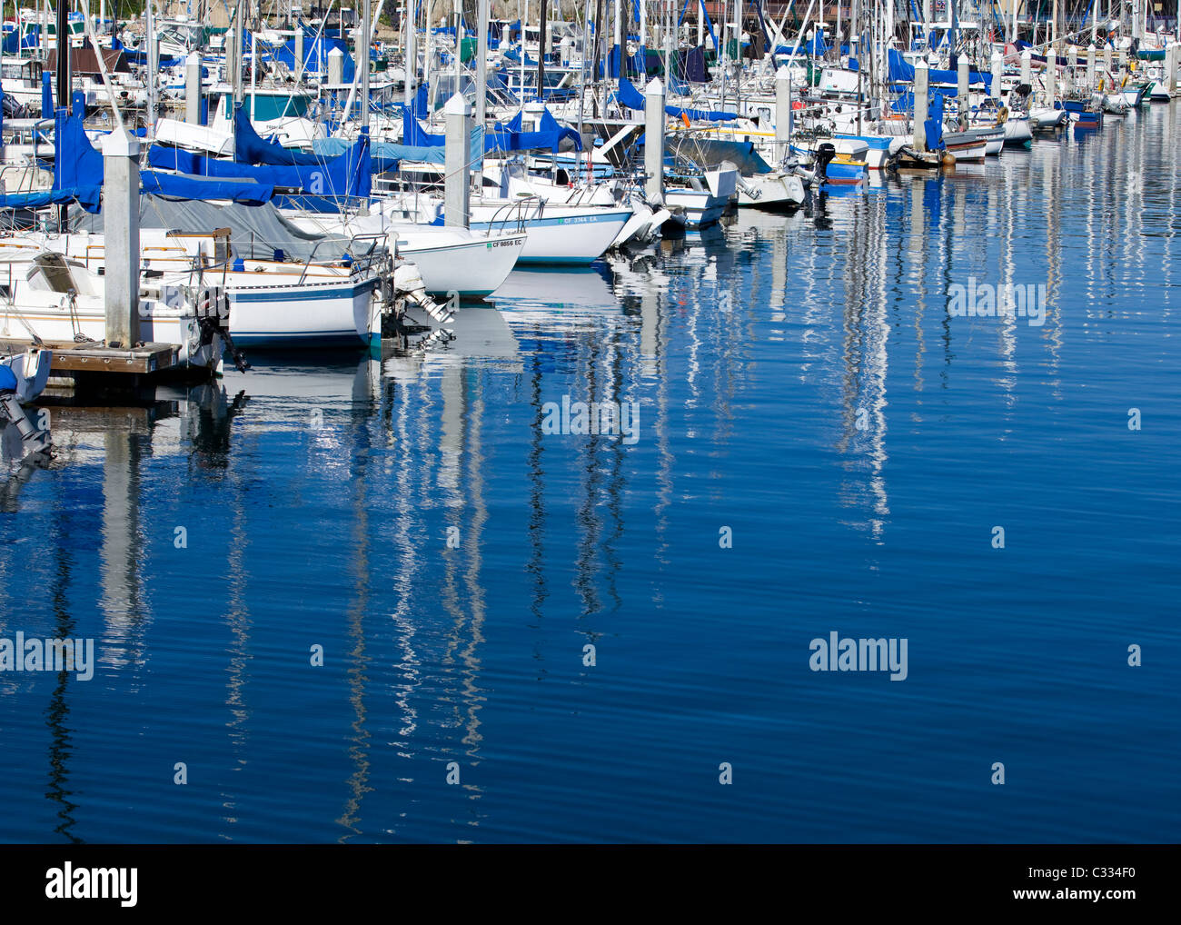 Small sail boats docked in marina slips - Stock Image