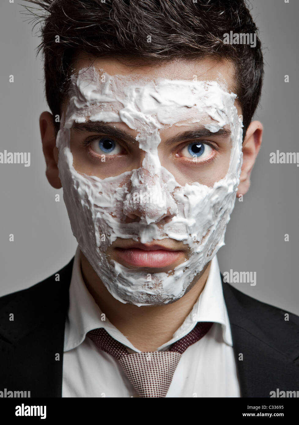 Portrait of a young businessman with a face full of shaved foam - Stock Image