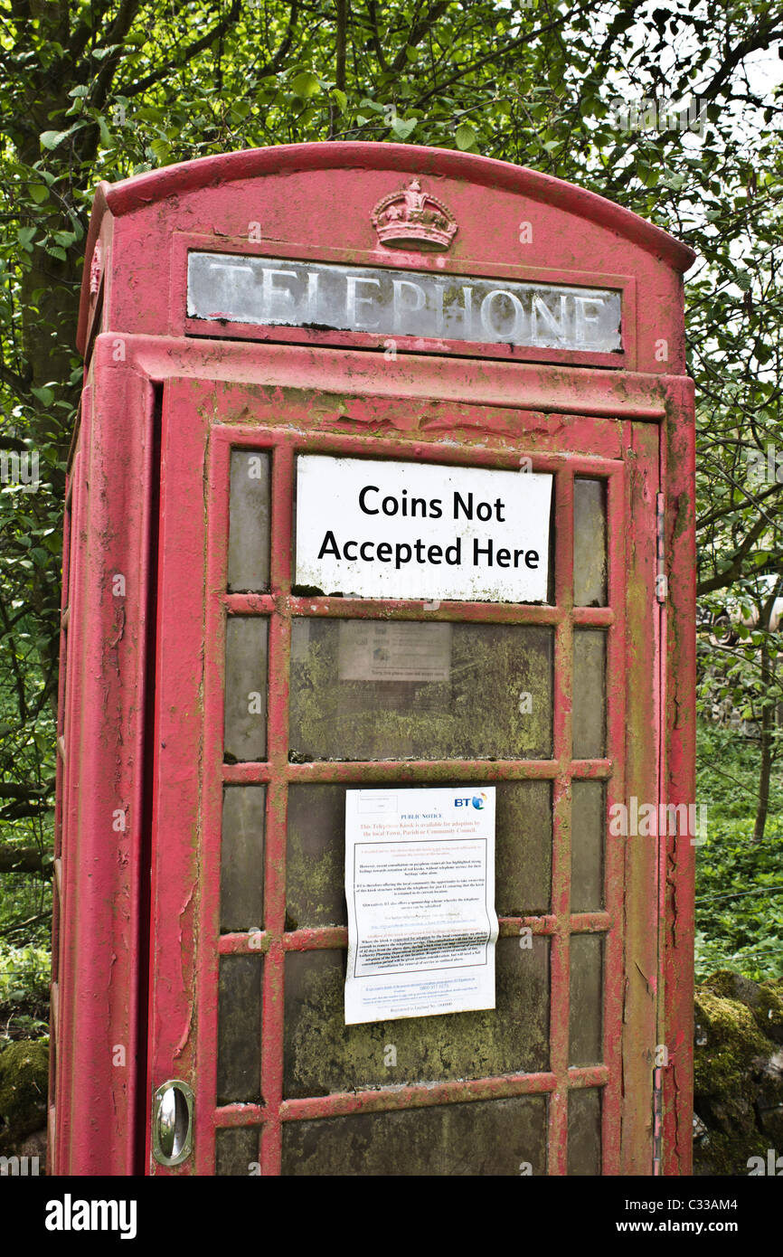 Neglected, faded red telephone box in a Scottish village with sign inviting the community to take it over (2011) - Stock Image
