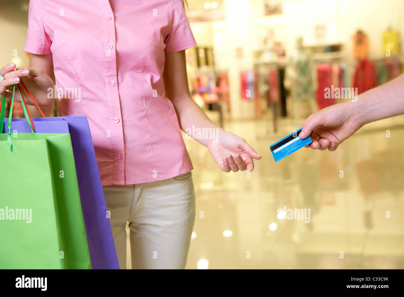 Close-up of woman taking plastic card from male hand in the mall - Stock Image
