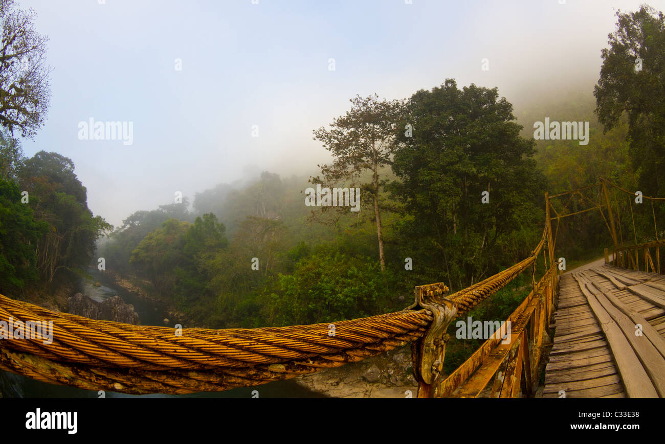 An old suspension bridge that crosses a jungle river in Guatemala - Stock Image