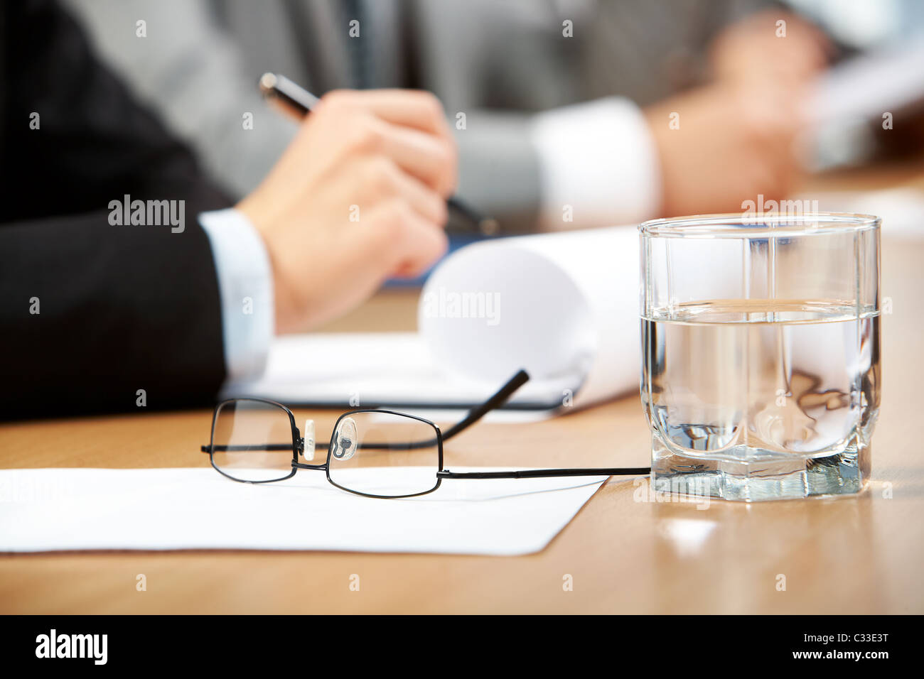 Image of human hand holding pen with glass of water, eyeglasses and paper near by - Stock Image