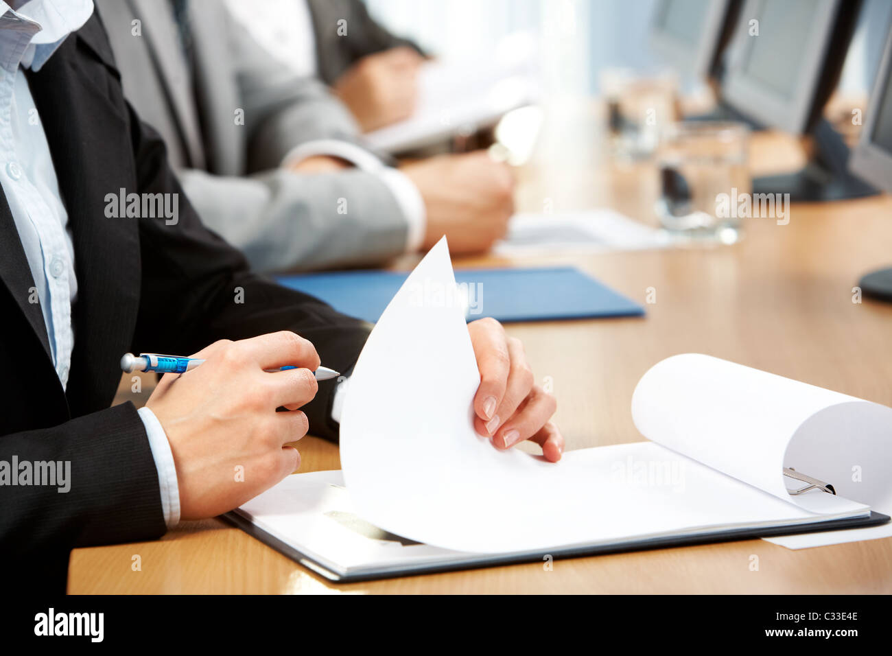 Image of human hand holding pen and making notes at conference - Stock Image