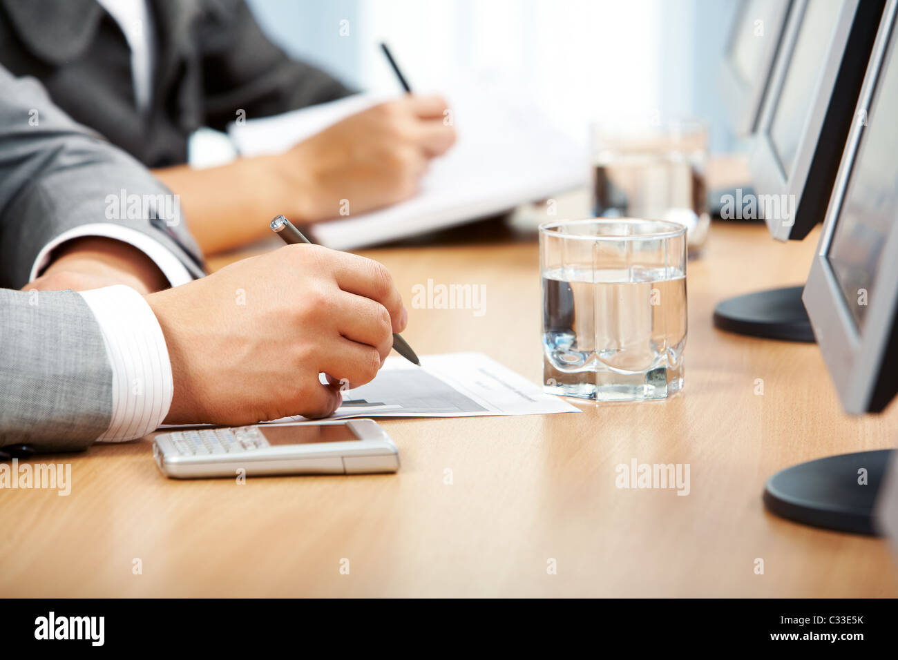 Image of human hand making notes with glass of water, cellphone and monitors near by - Stock Image