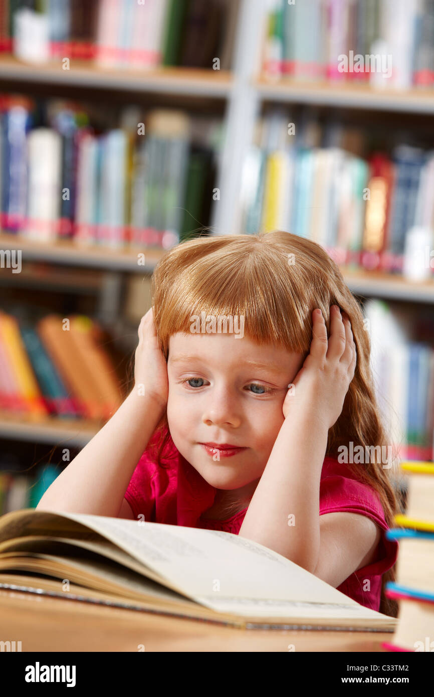 Portrait of smart girl reading book in library - Stock Image