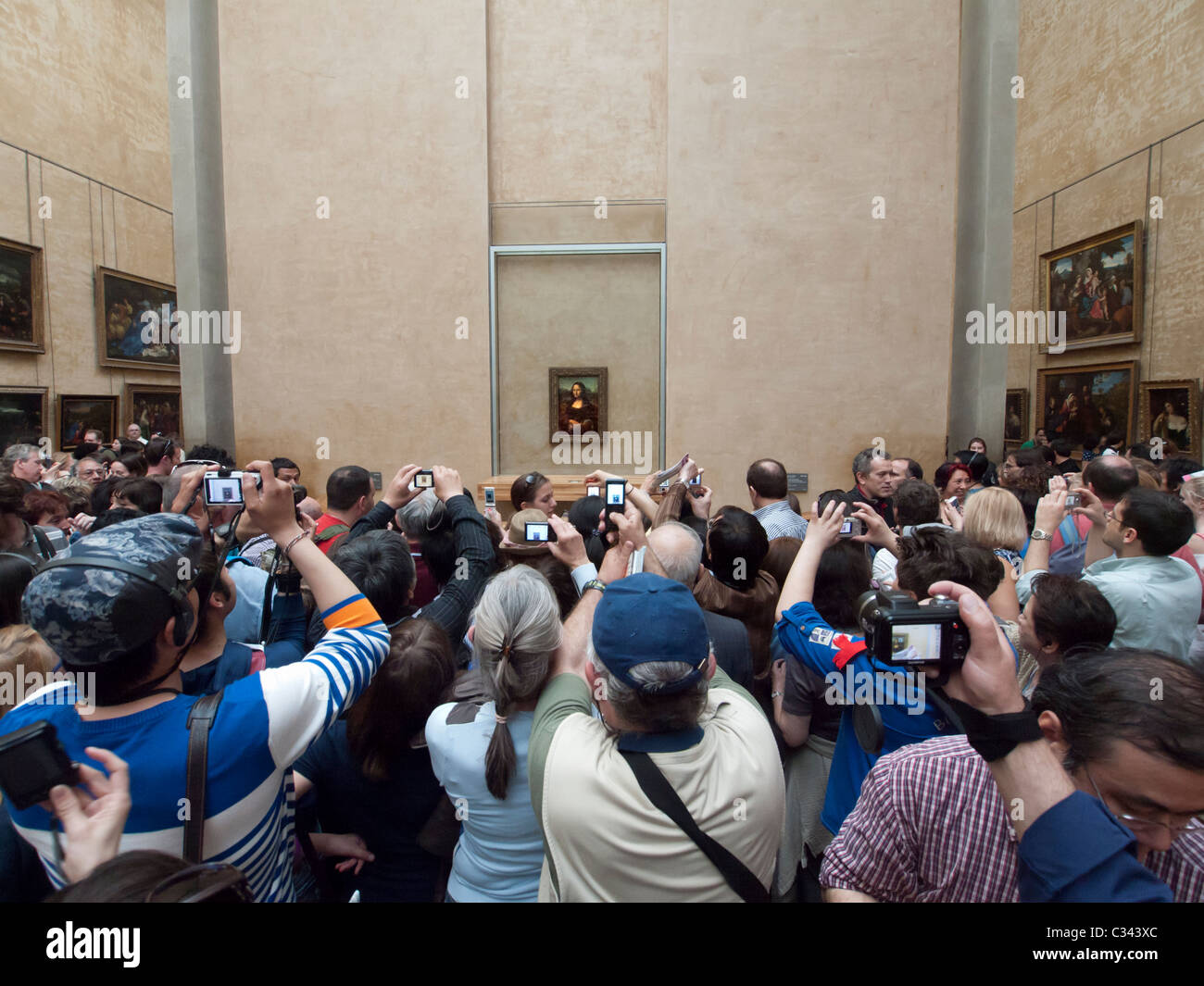 Huge crowds of tourists trying to see Mona Lisa painting by Leonardo da Vinci at The Louvre museum in Paris France - Stock Image