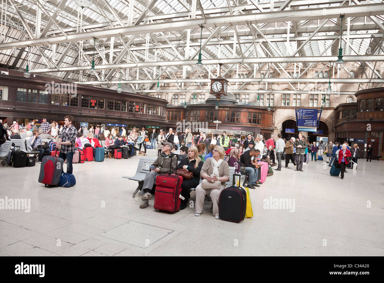 Passengers waiting for trains in the concourse at Glasgow Central Station. - Stock Image