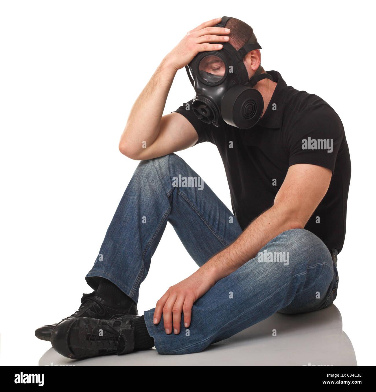 caucasian sit man wearing classic rubber gas mask - Stock Image