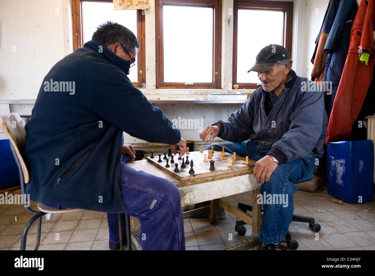 """Fishermen playing """"Checkers"""" board game. Also called """"Draughts"""" board game. Fishermen´s huts, Narsaq, South Greenland Stock Photo"""