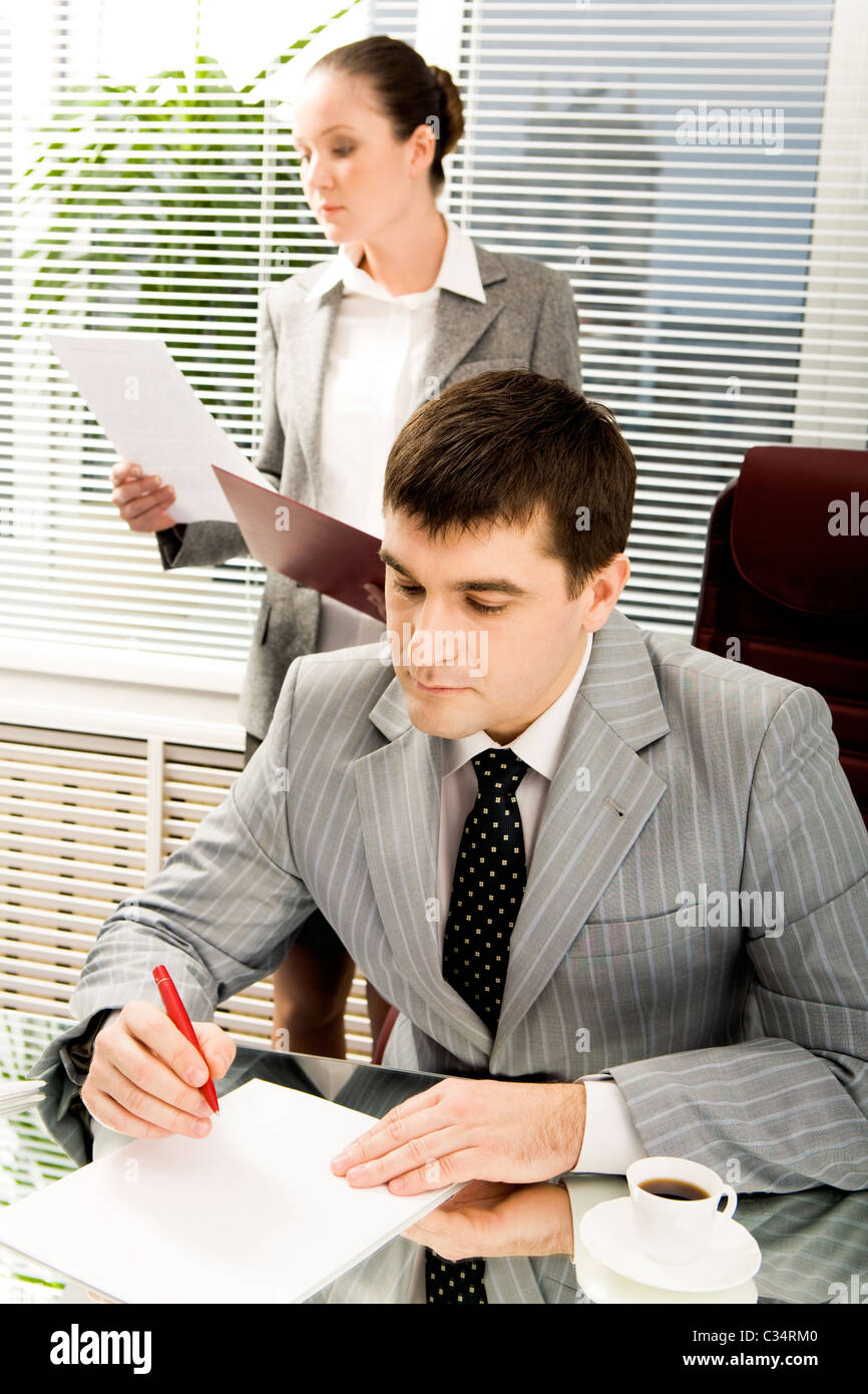 Portrait of serious boss signing contract with executive secretary on background - Stock Image