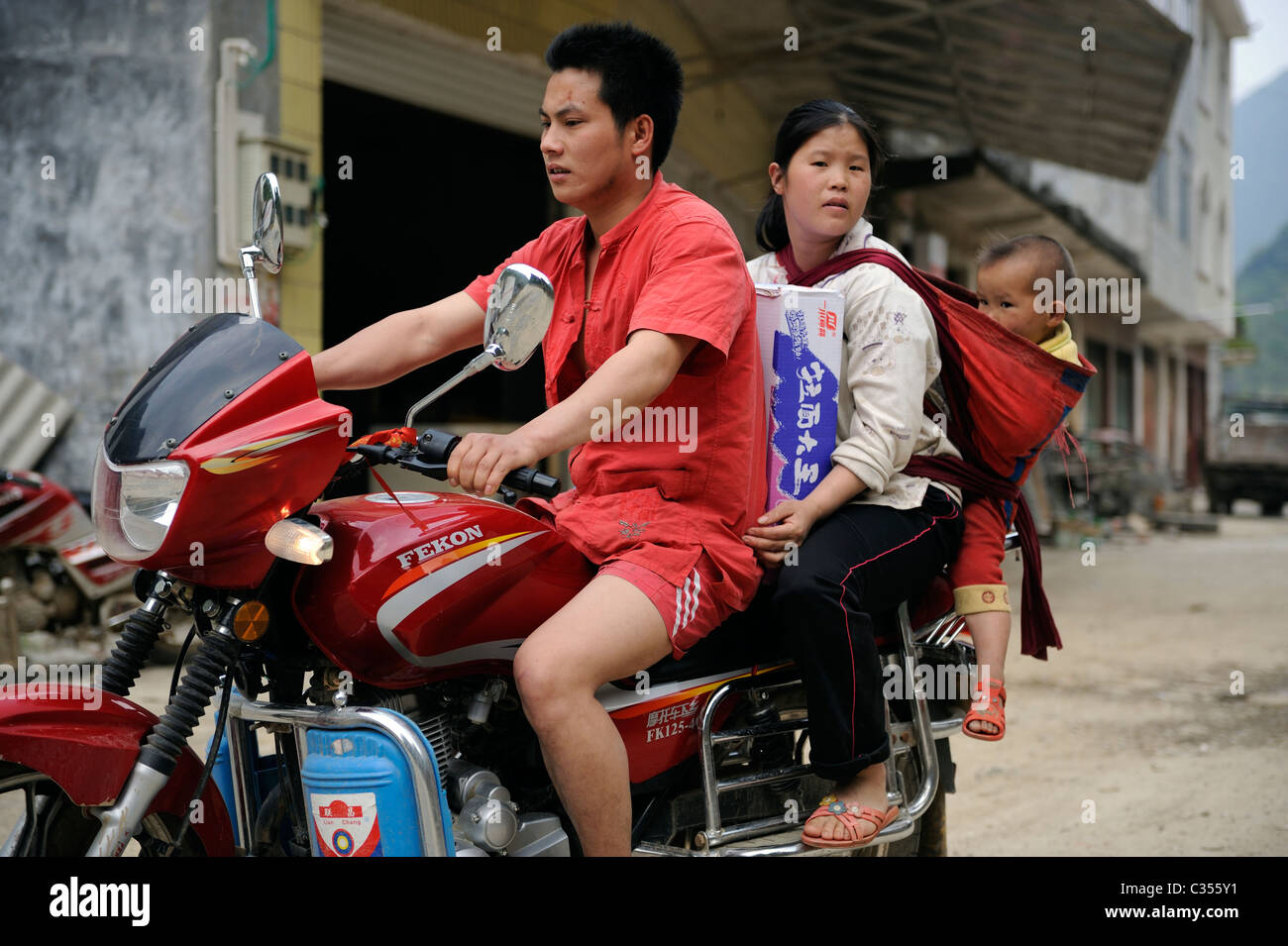 A man drives a motorcycle with his wife and baby in a remote countryside in Duan county,  Guangxi, China. 20-Apr - Stock Image