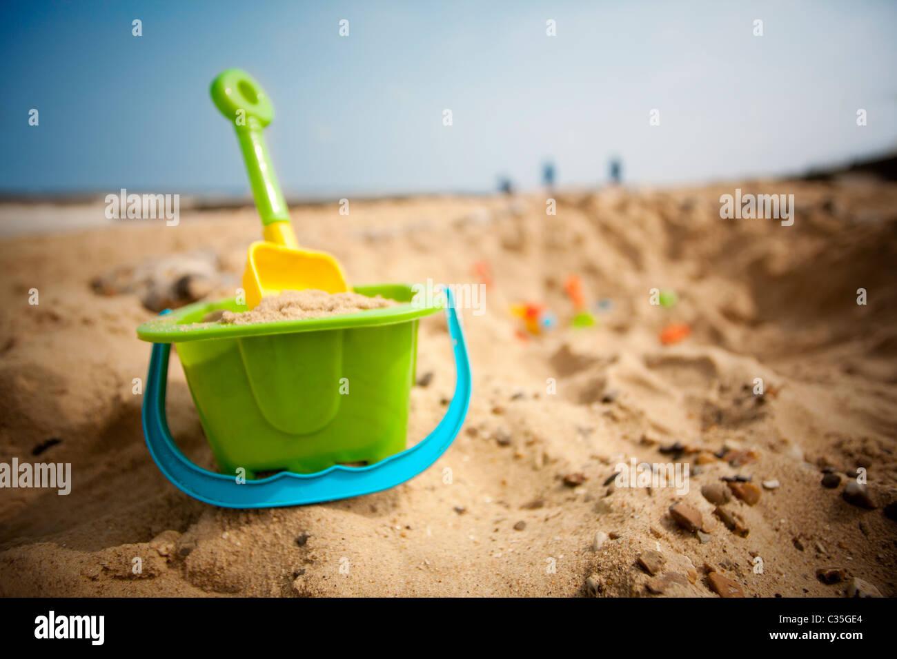Bucket and spade on beach - Stock Image
