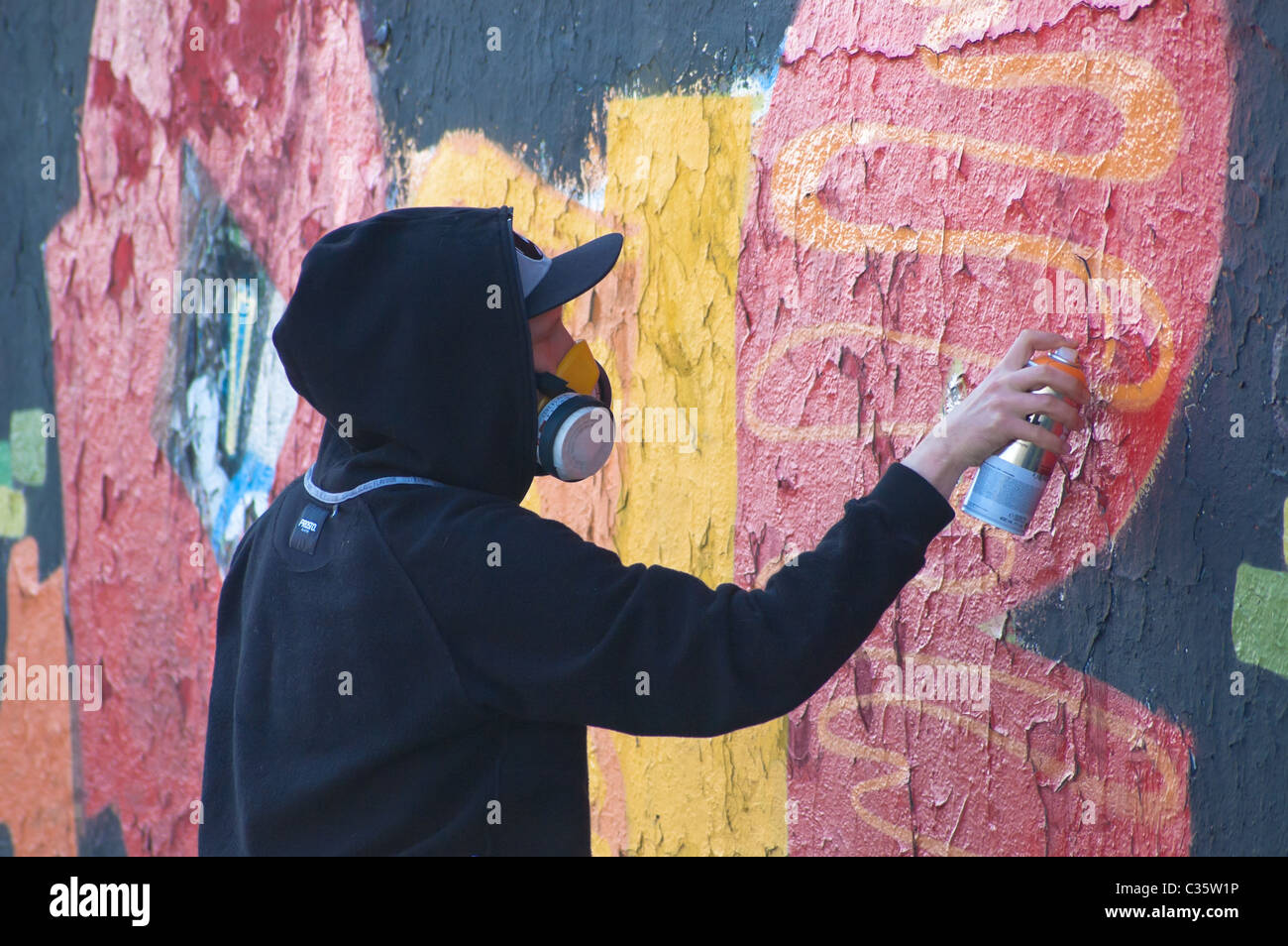 Young, masked man, while painting a graffiti on a wall. This wall surrounds Słuzewiec Horse Race Track in Warsaw - Stock Image