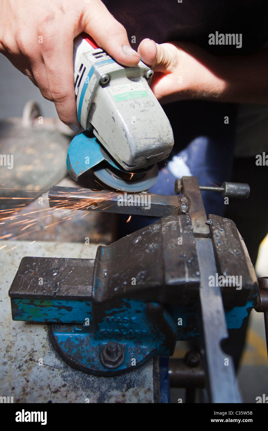 A person uses an angle grinder on metal held in a vice Stock Photo