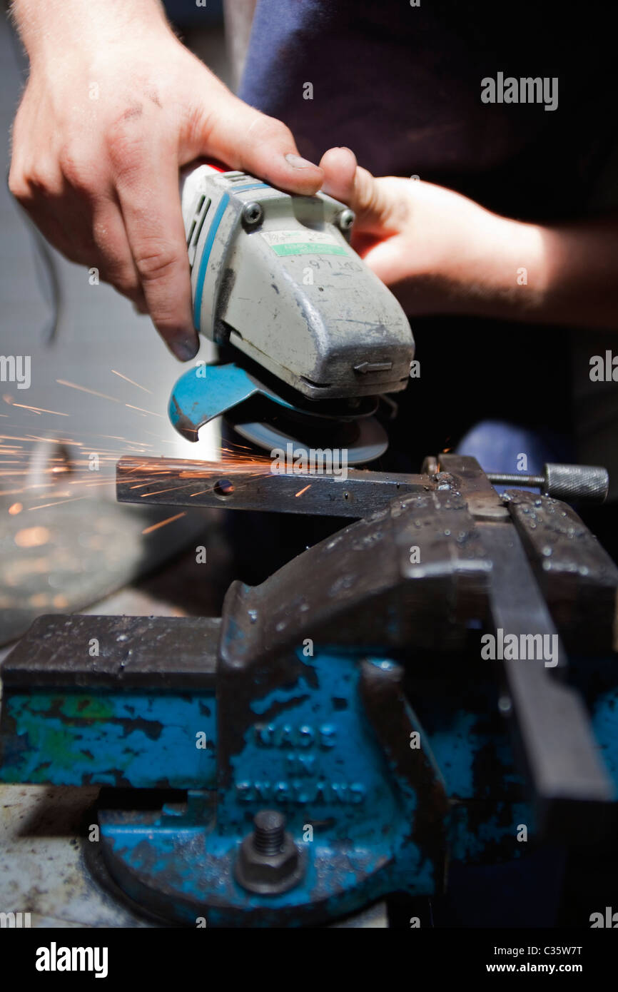 A person uses an angle grinder on metal held in a vice - Stock Image