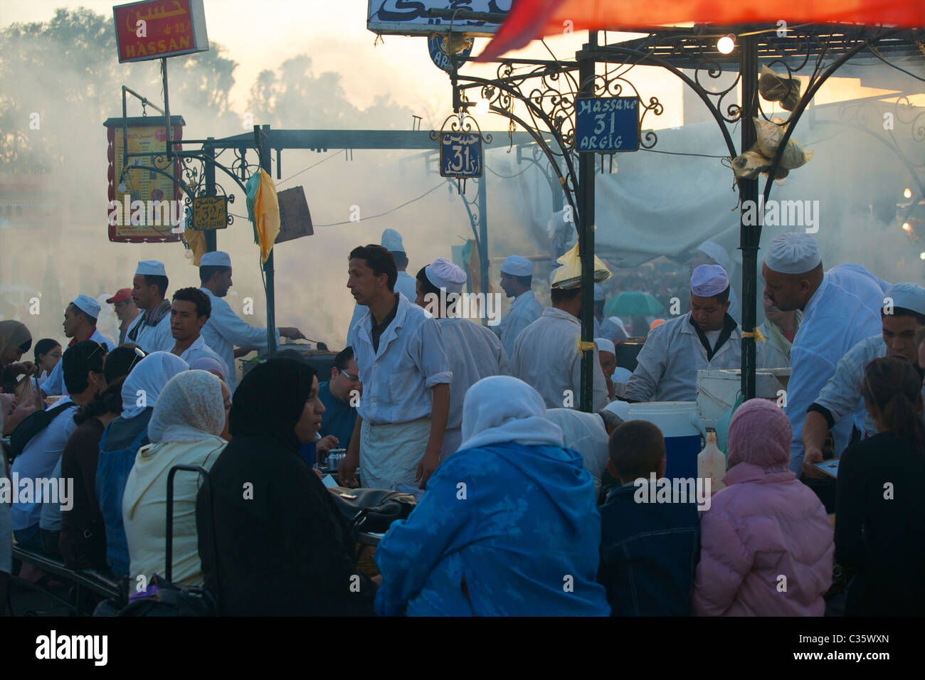 Bustling food stall in the main square, Marrakech, at dusk. - Stock Image