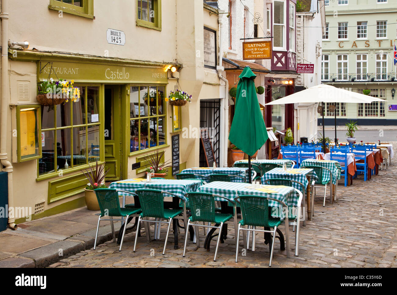 Tables and chairs outside a wine bar and restaurant in Church Lane, a small cobbled street in Windsor, Berkshire, England, UK Stock Photo