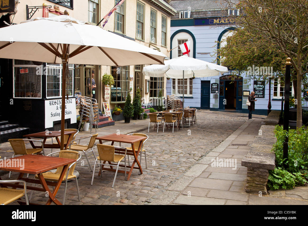 Tables and chairs outside restaurants in Church Street, a small cobbled street in Windsor, Berkshire, England, UK - Stock Image