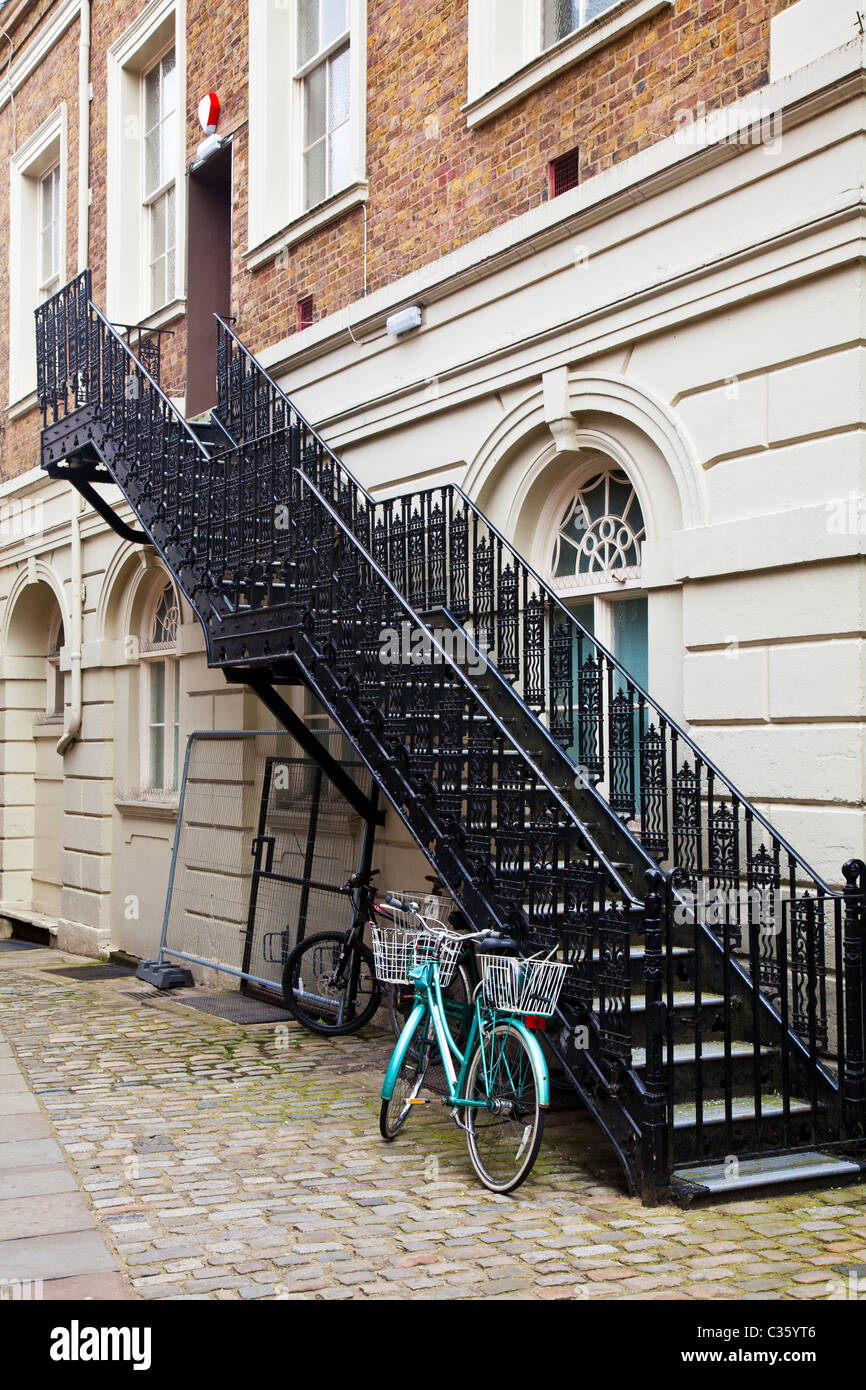 Green Bicycle Chained To A Black Wrought Iron Staircase In A Narrow Stock Photo Alamy