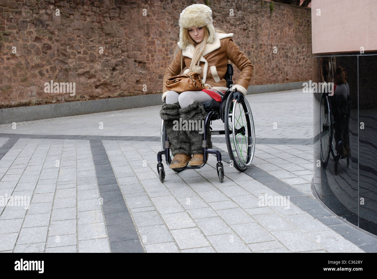 Young woman with the condition Friedreich's Ataxia using a wheelchair. - Stock Image