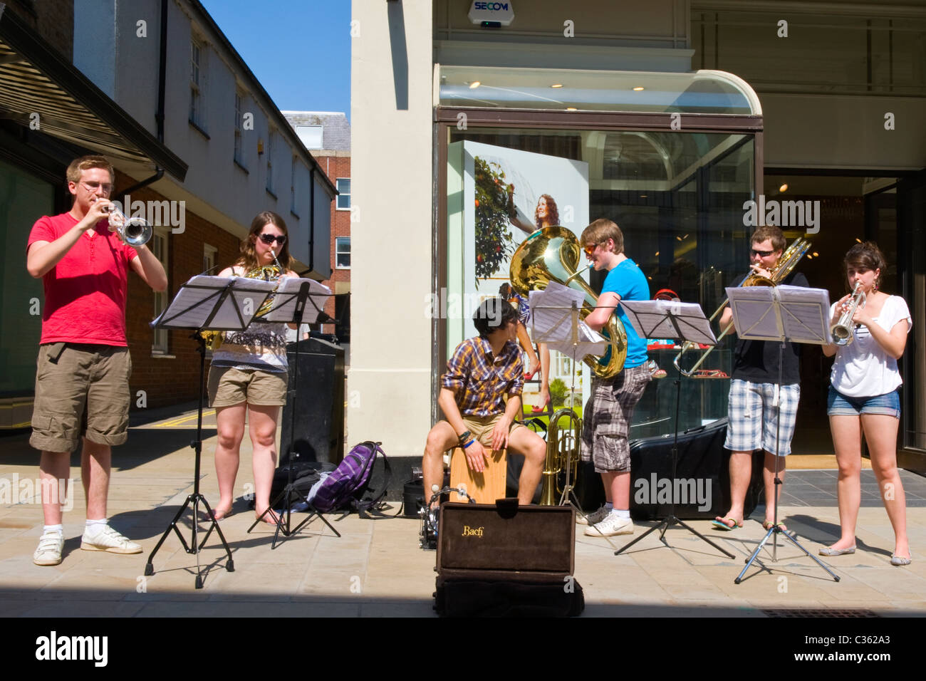 Winchester City High Street group of kids teenagers school children boys girls teenagers brass band busk playing - Stock Image