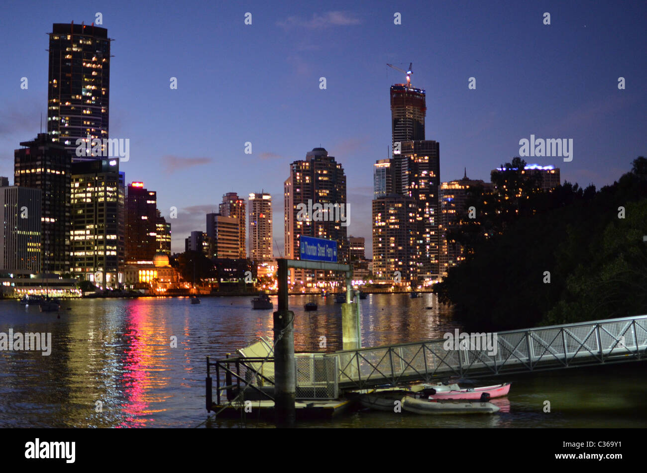 Brisbane city at night with the Brisbane River in the foreground. - Stock Image