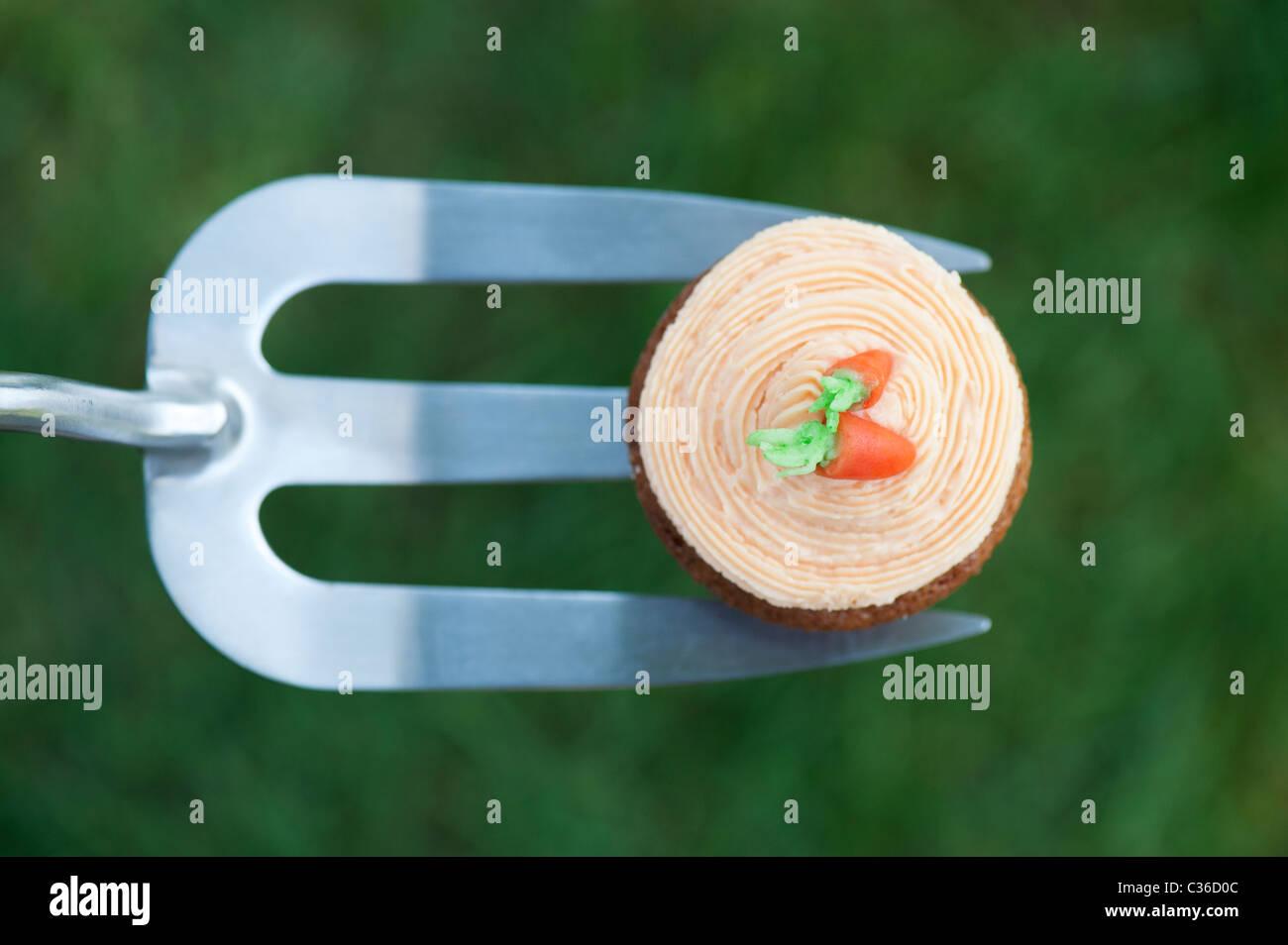 Carrot cupcake on gardening fork selective focus - Stock Image