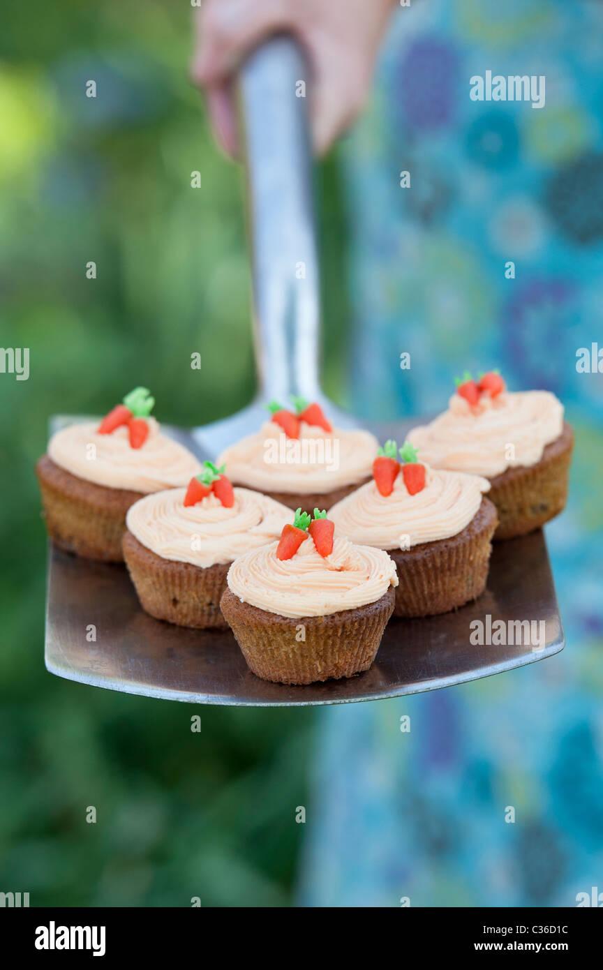 Carrot cupcakes on garden spade selective focus - Stock Image