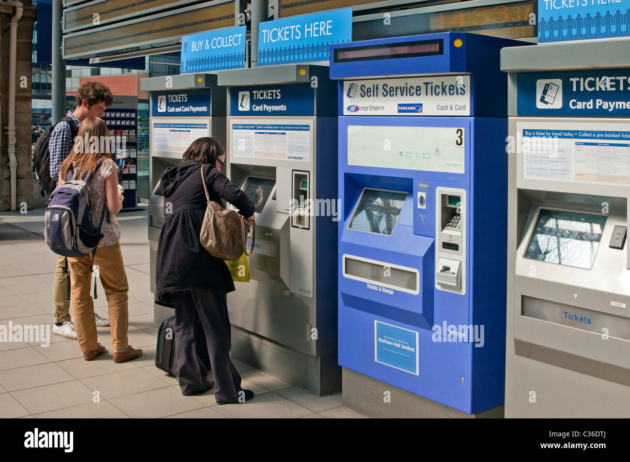 Collecting and buying tickets at railway station machines - Stock Image