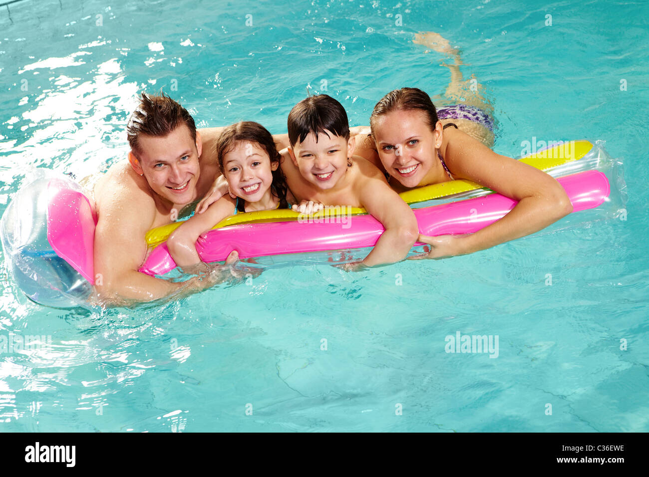 Cheerful family in swimming pool having nice time - Stock Image