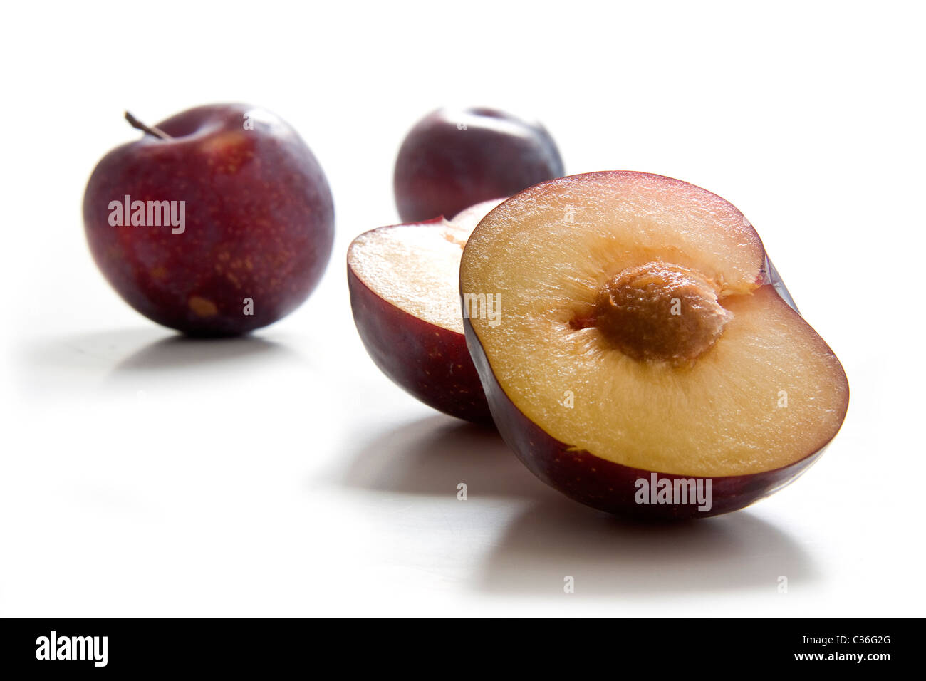 Two whole and half plums, variety Calita - Stock Image