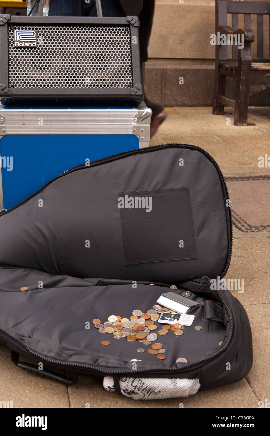 Money collected by busking in a buskers guitar case in the Uk - Stock Image