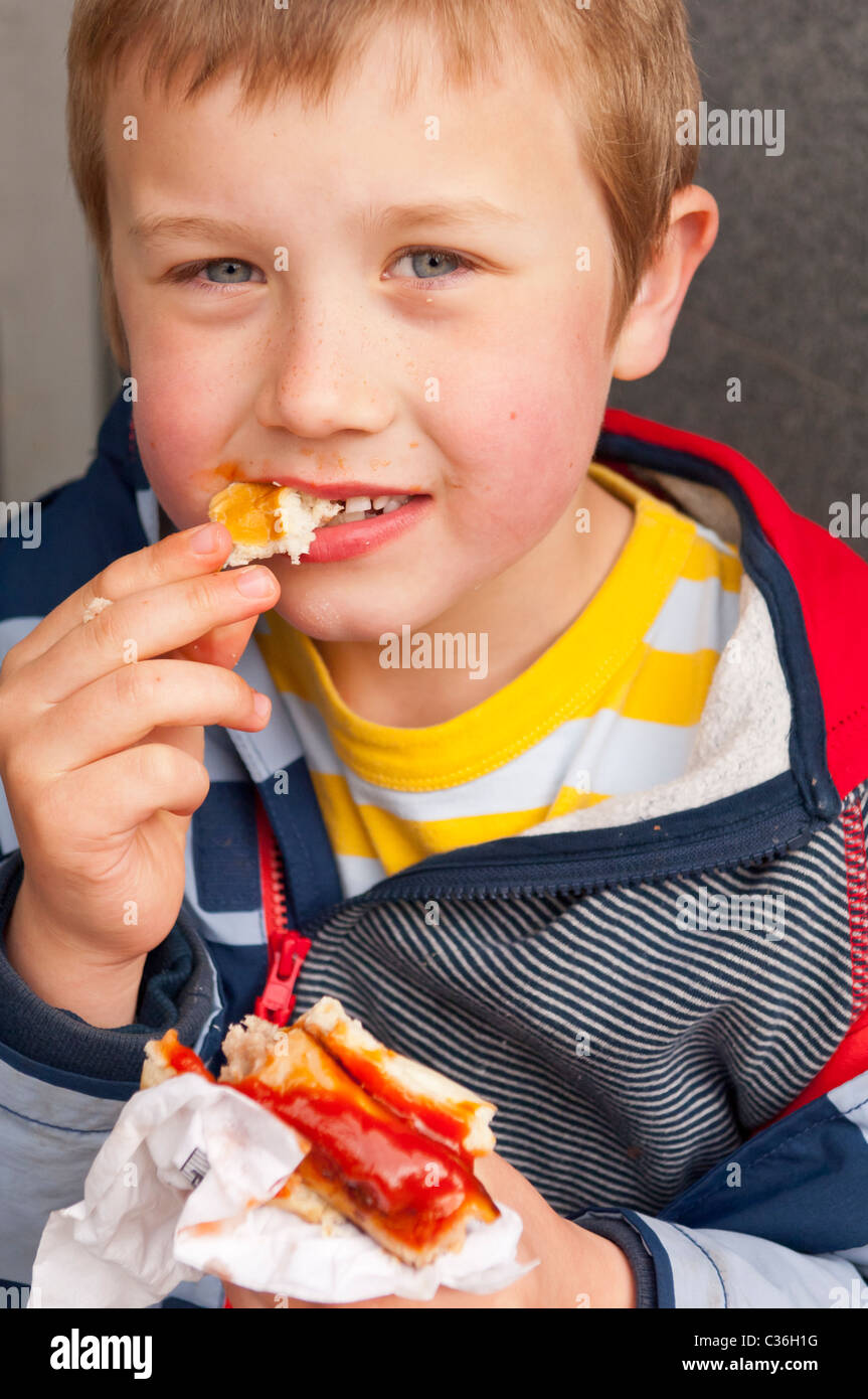 A seven year old boy eating a hot dog with tomato ketchup sauce in the Uk - Stock Image