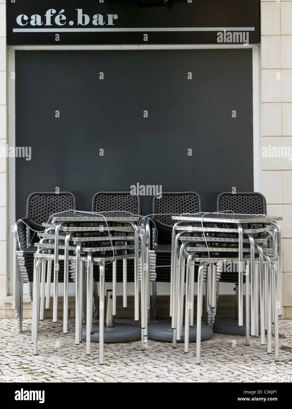 Chairs And Tables Stacked Up Outside A Closed Café Bar   Stock Image