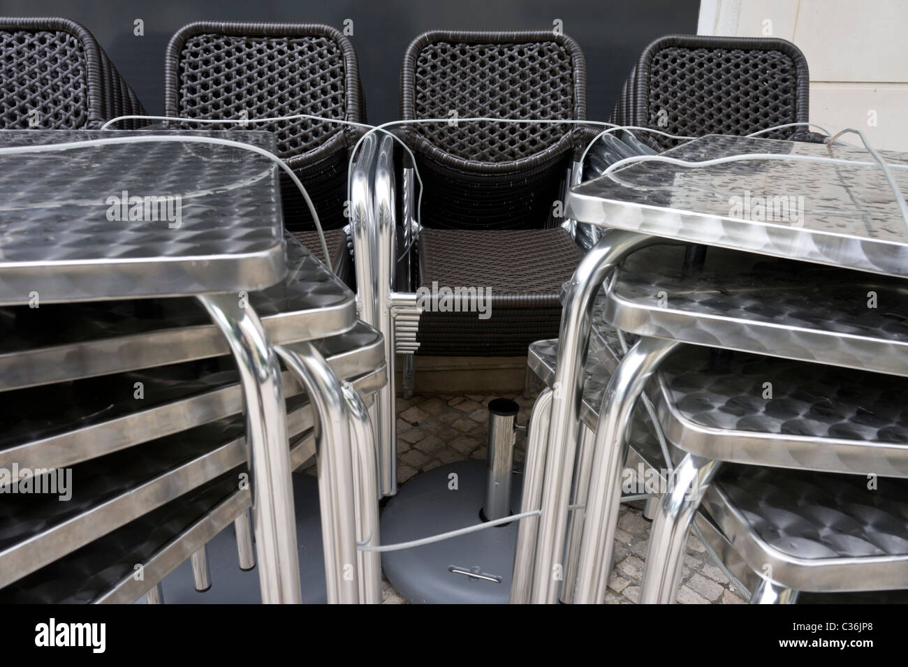 Chairs and tables stacked up outside a closed café bar - Stock Image