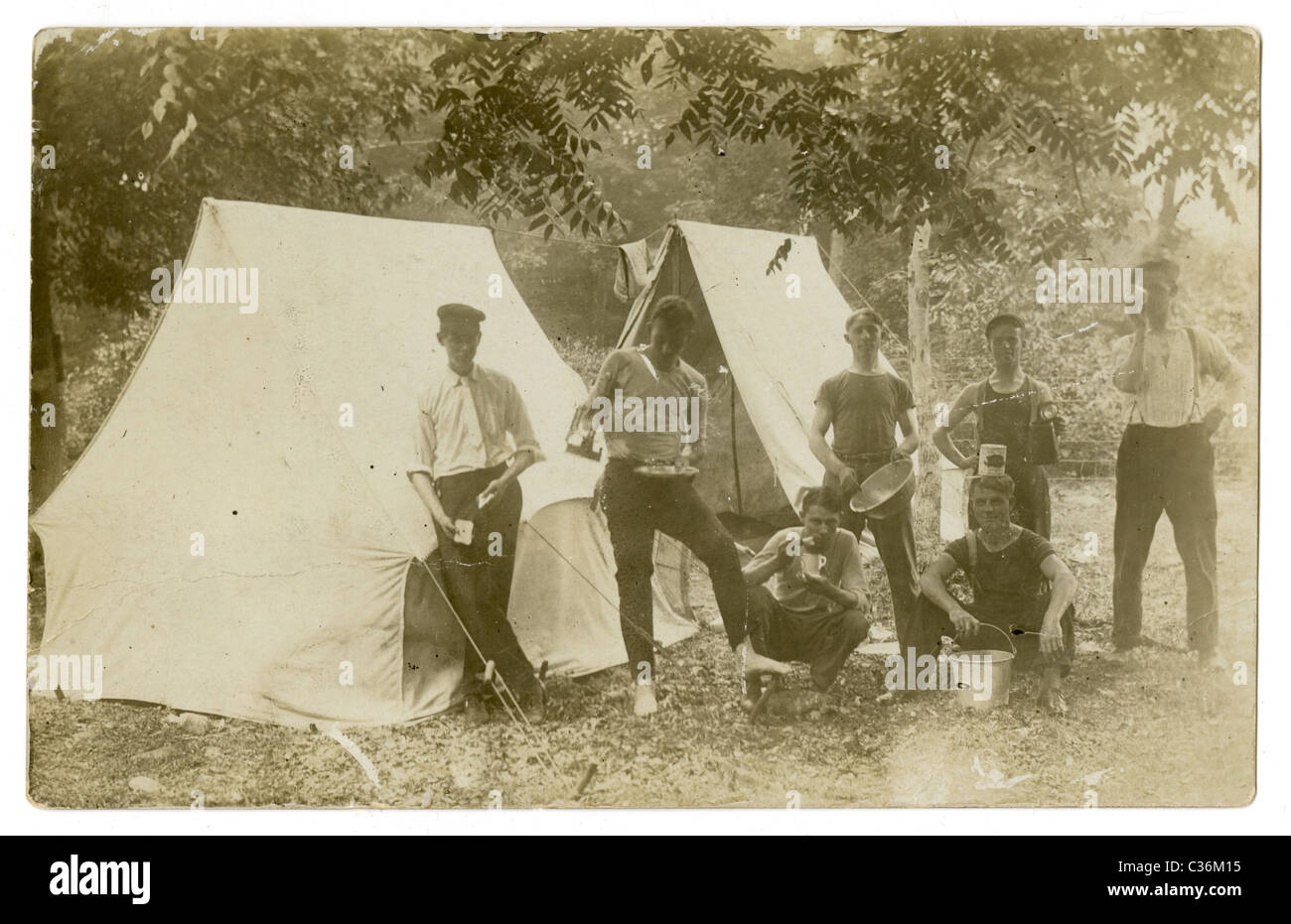 Circa 1910s real-photo post card showing a group of 7 men camping. - Stock Image