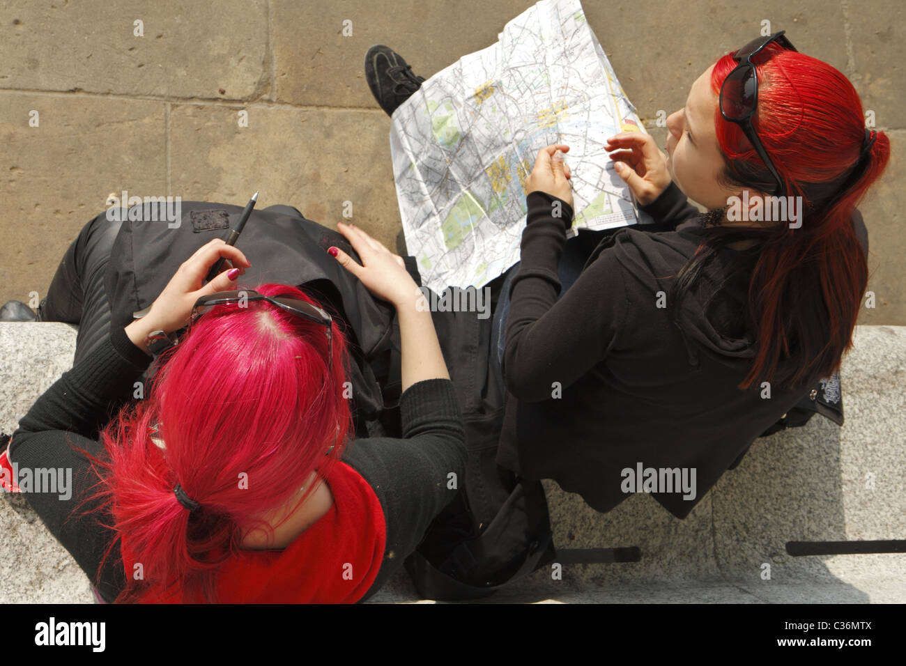 Two young female tourists with dyed red hair consulting a map, London, UK - Stock Image
