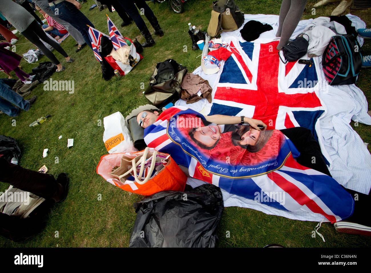 royal wedding reveller asleep under flag of Catherine Middleton and Prince William hyde park - Stock Image