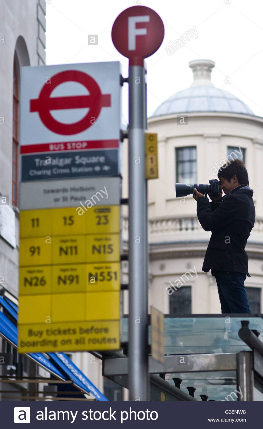 Royal wedding street scene 2011 April 29 London UK Man standing on roof of bus stop taking a picture with a digital - Stock Image