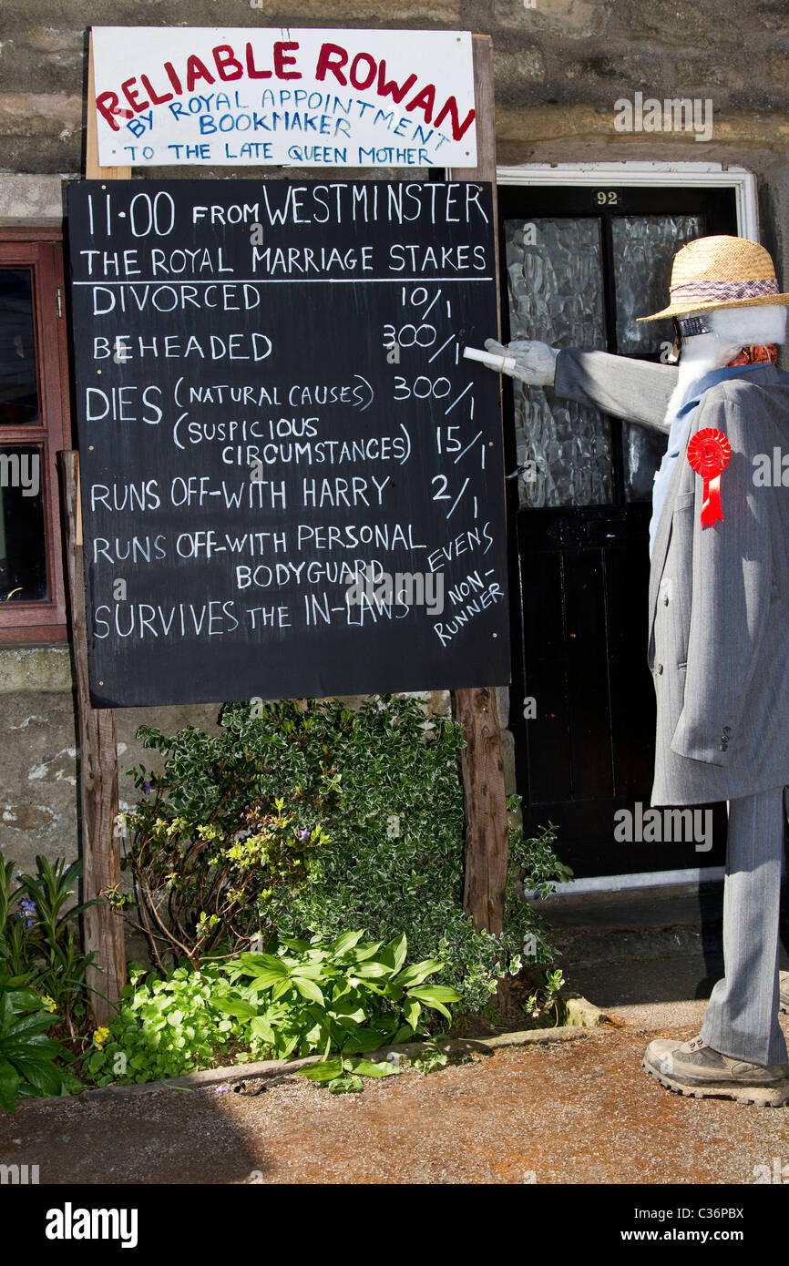 People walking past Bookmakers display in High Street _Betting odds at the Wray Annual Scarecrow and Village Festival, - Stock Image