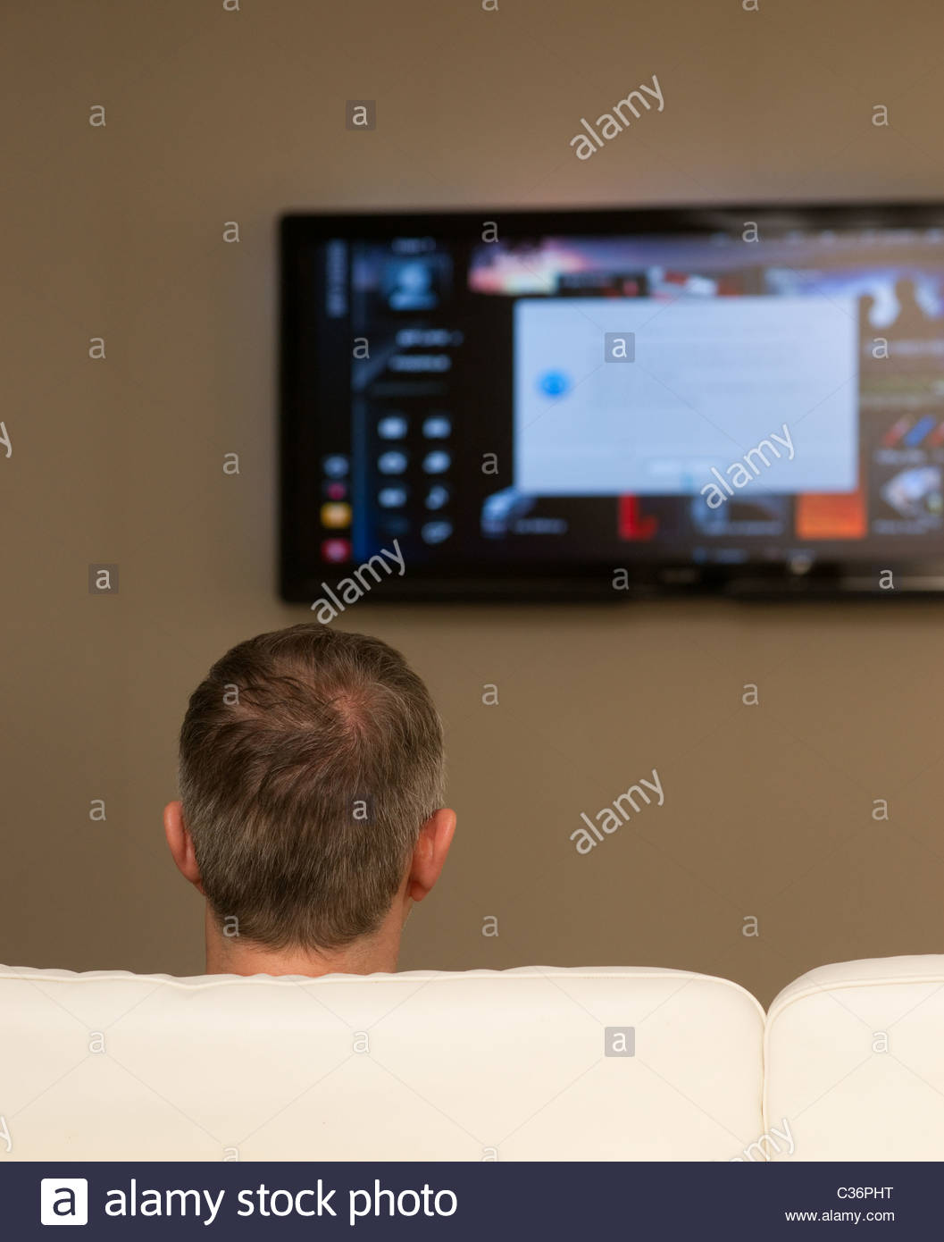 Man watching big screen television tv watch home flat screen wall sofa couch - Stock Image