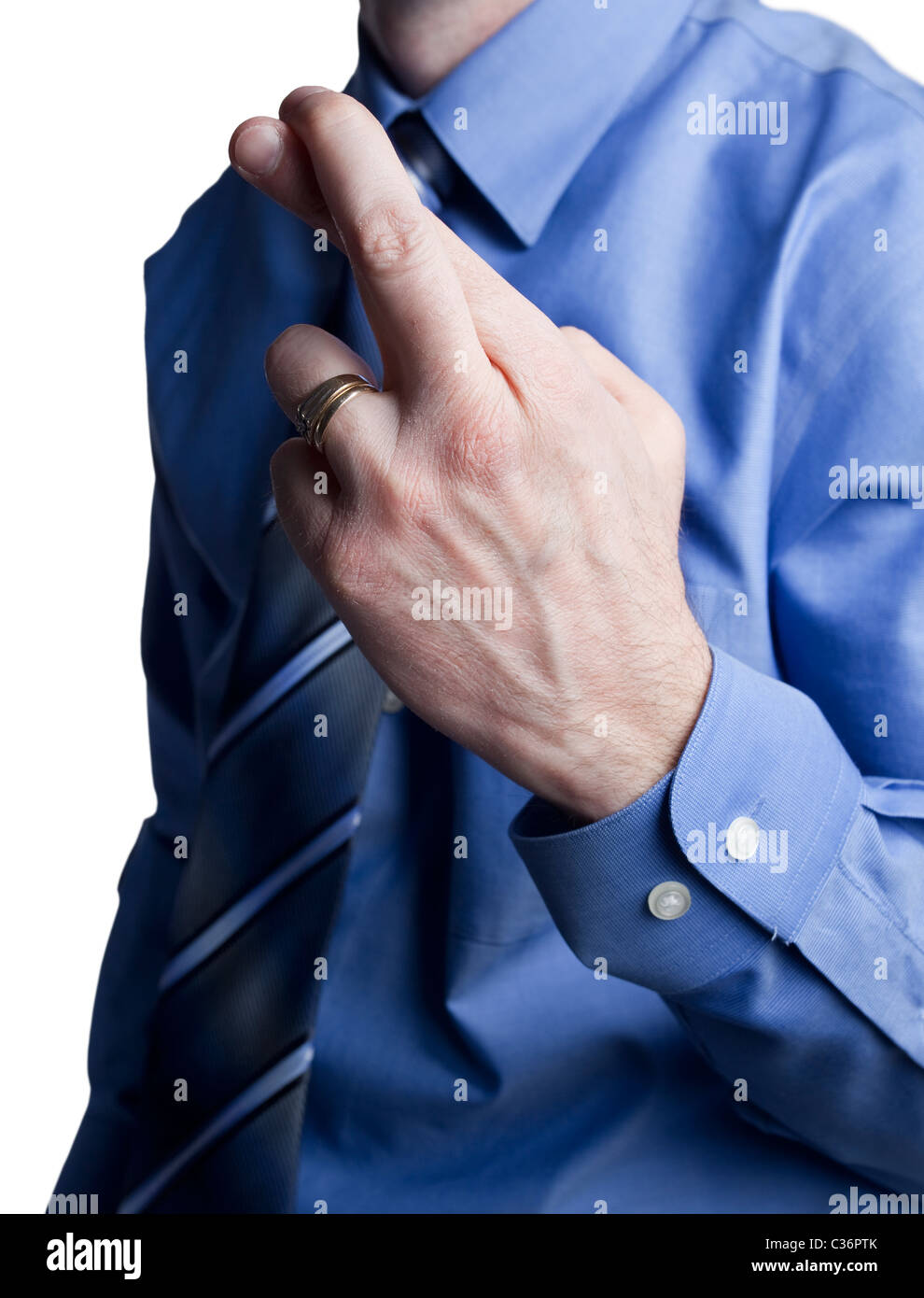 business man in a blue shirt and tie with crossed fingers for good luck - Stock Image