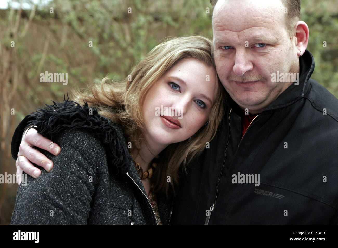 Portrait of an older man hugging a younger woman - Stock Image