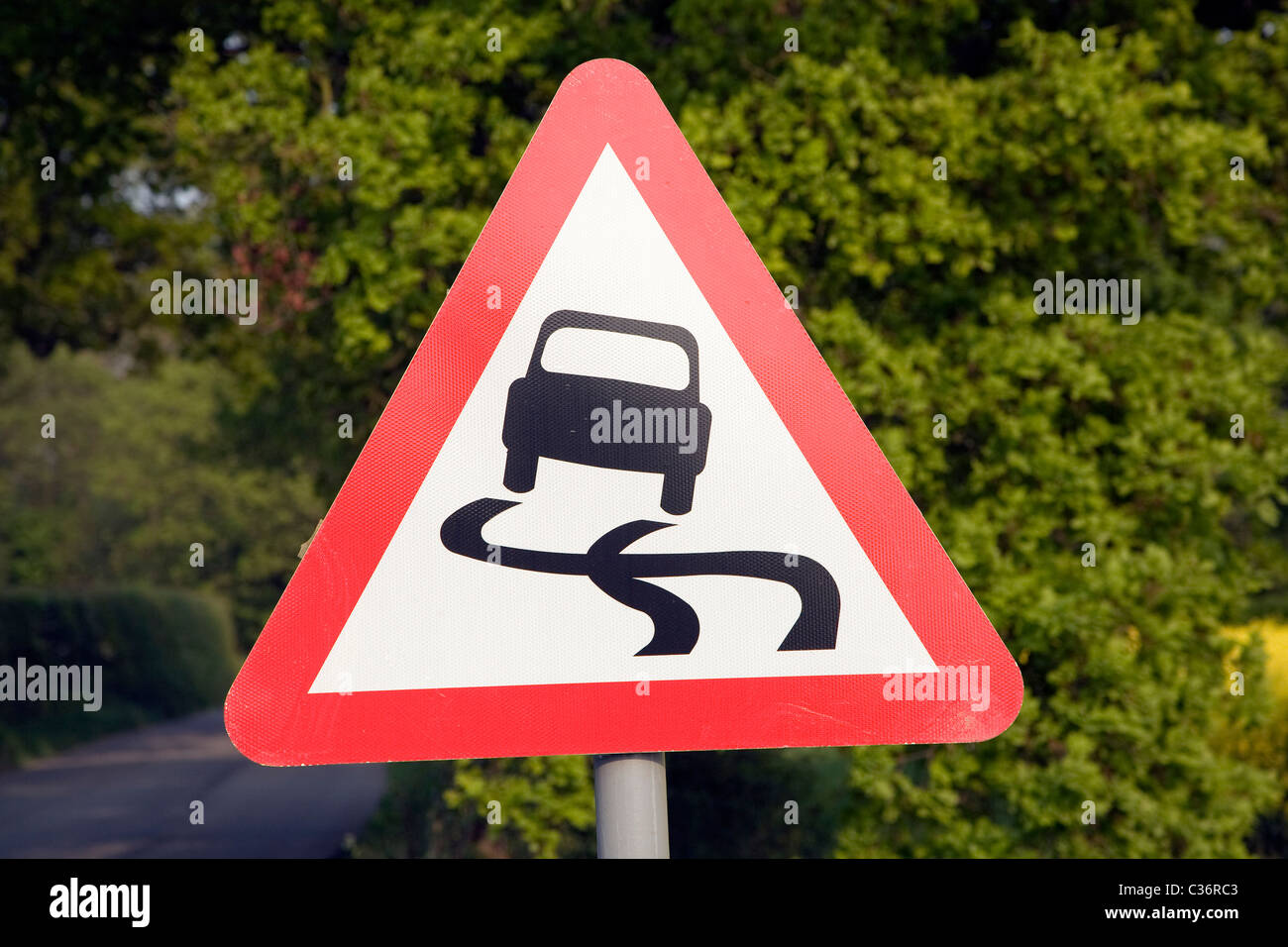 Red triangle road sign for risk of skidding - Stock Image