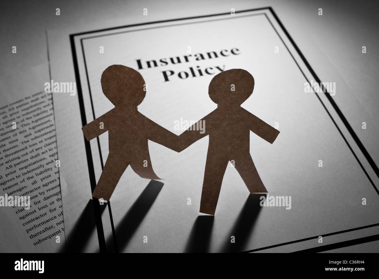 Insurance Policy and Paper Chain Men close up - Stock Image
