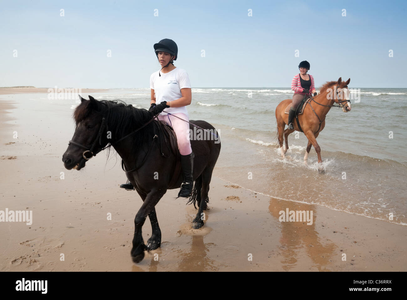Two girls riding their horses on Holkham beach, North Norfolk, UK Stock Photo