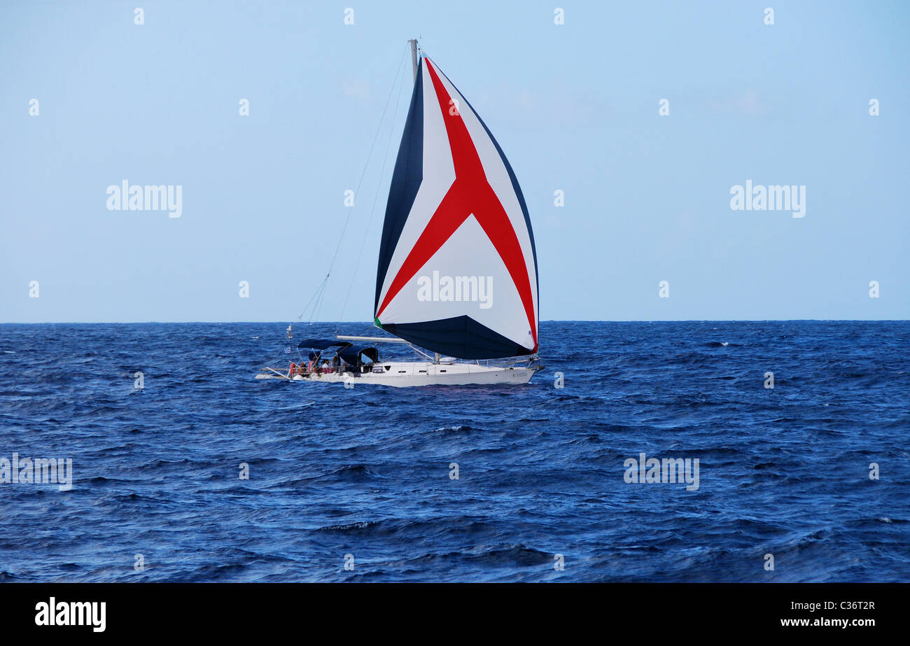 Sailing Yacht with blue, red and white sail passaging from Paxos to Corfu, Ionian Sea, Greece - Stock Image